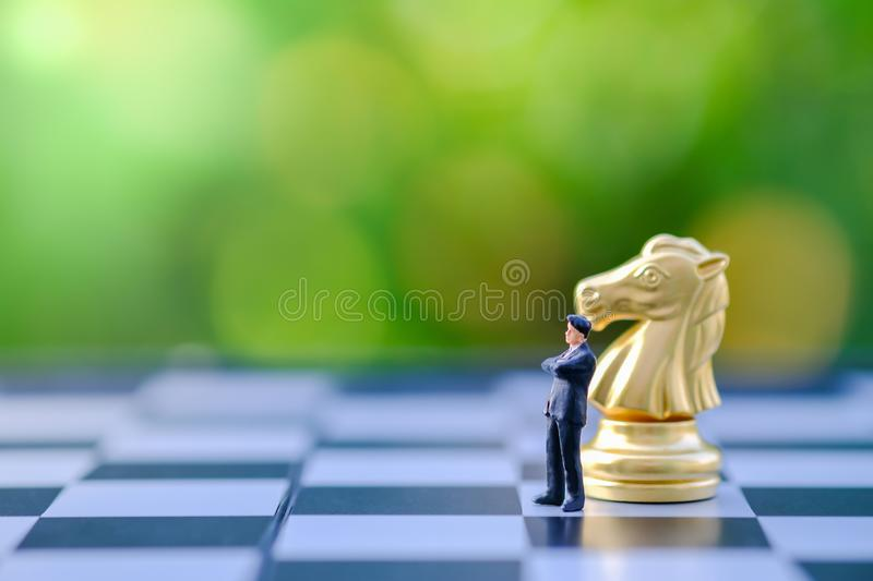 Business, Planning, Global, work and strategy concept. Close up of businessman miniature figure standing and thinking on. Chessboard with gold knight chess royalty free stock images