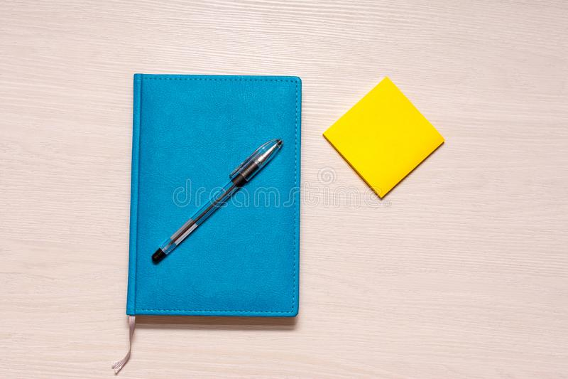 Closed diary of turquoise color with a black pen on top and yellow stickers on the right, top view royalty free stock photo