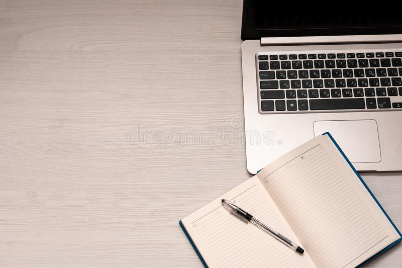 Opened notebook with black pen and silver laptop on a white wooden table, top view, copy spase stock image