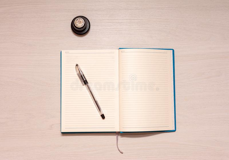 Opened notebook with black pen and official stamp on a white wooden table, top view stock photo