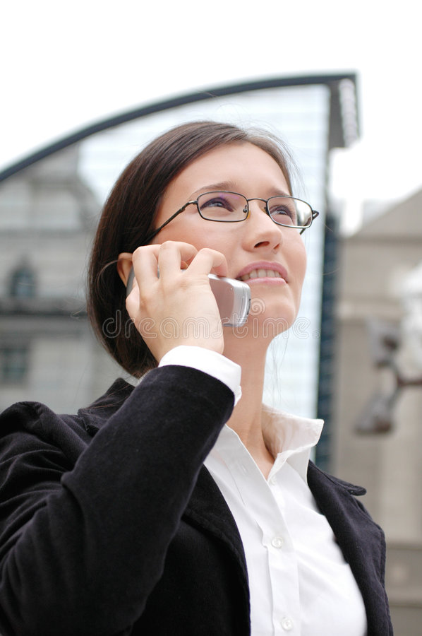 Business portrait. Young business woman discussing on the phone. Modern architecture blurred in the background