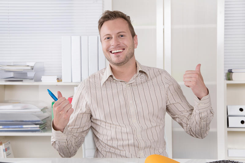 Business: Portrait of young successful man with thumbs up in of royalty free stock photo