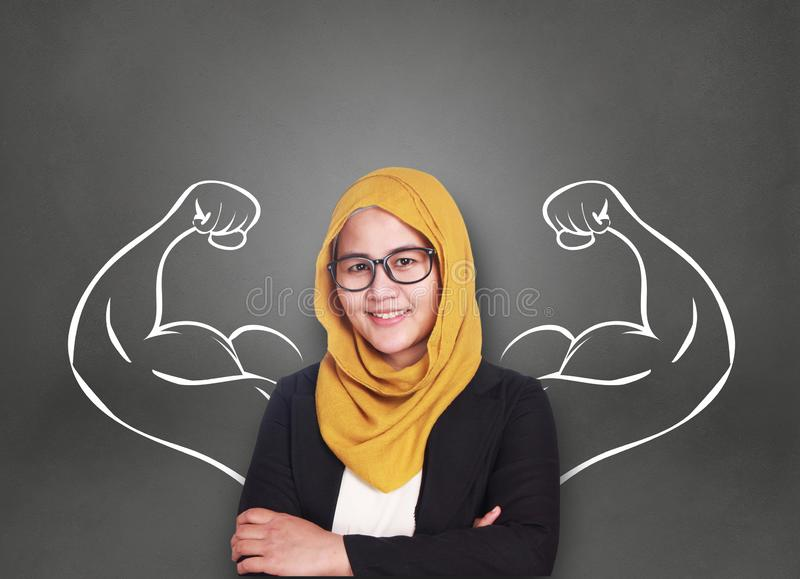 Businesswoman with Strong Inner Power. Business power concept. Young Asian muslim businesswoman smiling with strong powerful arms drawn behind. Inner power stock photos