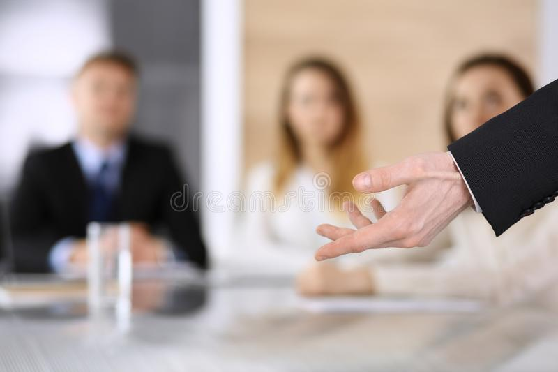 Business presentation. Businessman giving speech to colleagues and partners at corporate meeting or conference, close-up stock photography