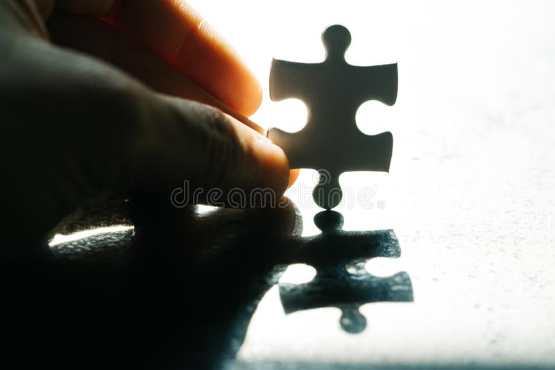 Business problem, obstacle and solution for success metaphor, ha. Nd holding a paper jigsaw puzzle piece with hoping sun light, the one that solve problem royalty free stock photography