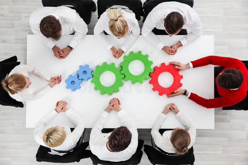 Business problem solution concept. Business problem solution, mechanism of business, teamwork concept, business team sitting around white table with cogs royalty free stock photos