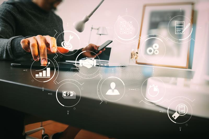 Businessman working with smart phone and digital tablet and laptop computer in modern office. Business process management with workflow automation diagram and stock photos