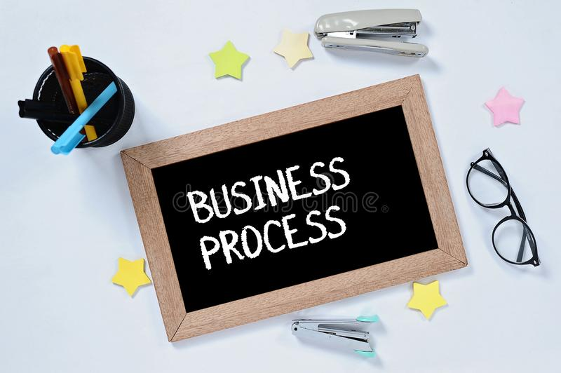 BUSINESS PROCESS word on top view of blackboard with glasses, pen case, staplers and marker royalty free stock photos