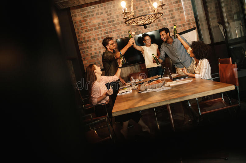 Business professionals celebrating success with beers. Group of business professionals celebrating success with beers. Young people having a party in startup stock photography