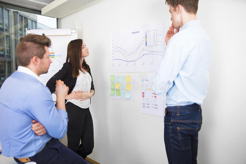 Business Professionals Discussing Over Line Graph In Office royalty free stock image