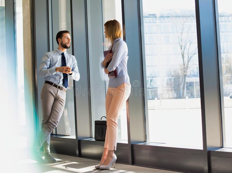 Business professionals discussing plans while leaning on window in office hall. Photo of Business professionals discussing plans while leaning on window in royalty free stock images