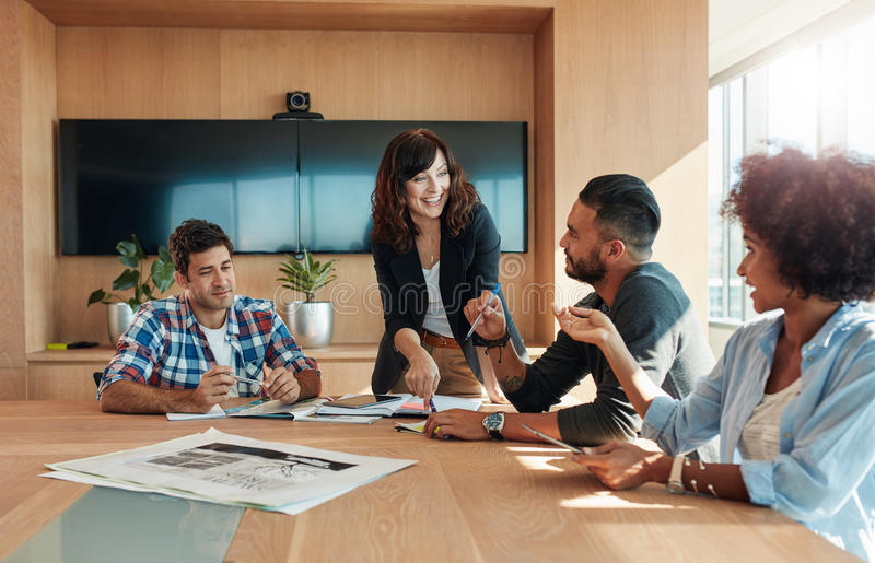 Business professionals having a meeting in boardroom. Shot of a group of young business professionals having a meeting in boardroom. Office workers discussing stock photos