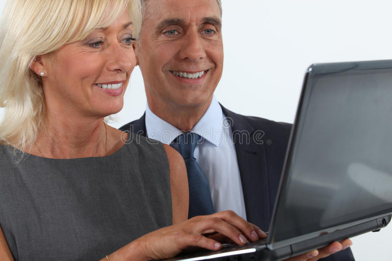 Business professionals looking at a laptop. Smiling business professionals looking at a laptop stock image