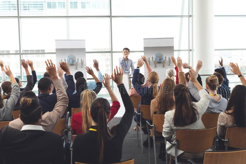 Business professionals raising hands in a business seminar royalty free stock photo