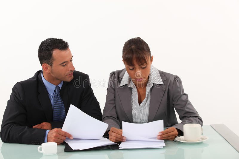 Business professionals reviewing reports. Business professionals reviewing a report royalty free stock image