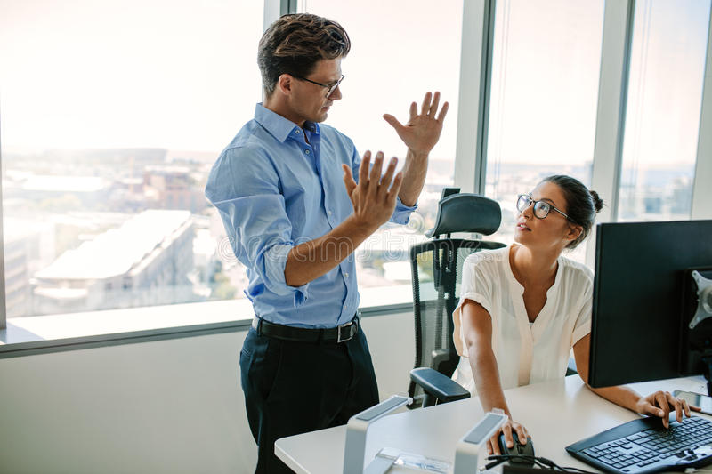 Business professionals working together in office. Mature men explaining new business strategy to asian female colleague sitting at her desk. Two business stock image
