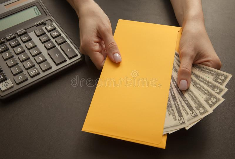 Business and profit concept with calculator, money in envelope in female hands, close-up stock photo