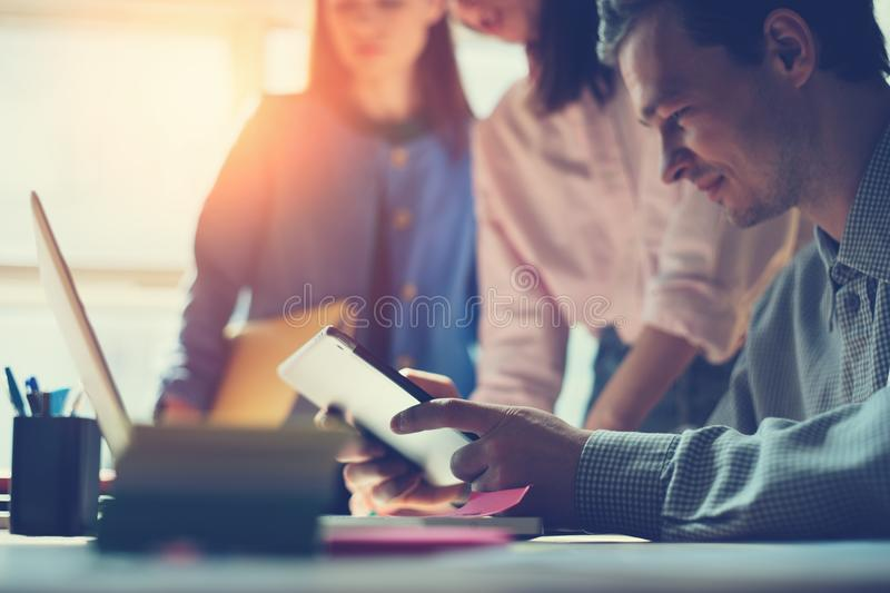 Marketing team discussing new working plan. Laptop and paperwork in open space office. Man sitting with tablet PC royalty free stock photography