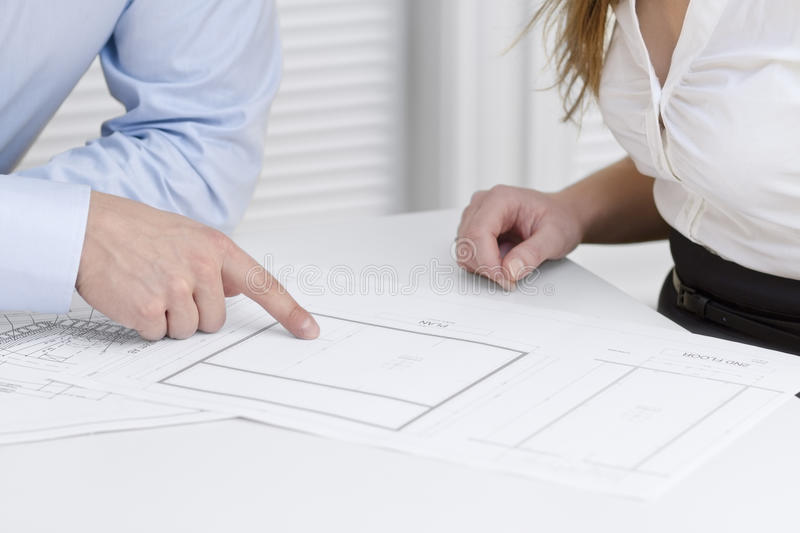 Business Project Meeting. A businesswoman and a businessman in a meeting. Teamwork. Pointing and looking at a printed architect drawing on a table stock image