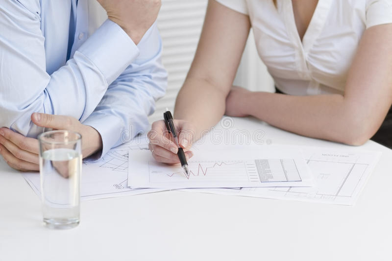 Business Project Meeting. A businesswoman and a businessman in a meeting. Teamwork. Pointing and looking at a printed diagram on a table stock images