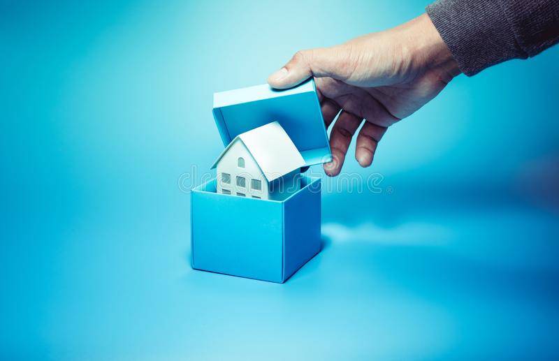 Business property and real estate concepts with male hand open box and you can see white model house inside. Over all on pastel color background stock photo