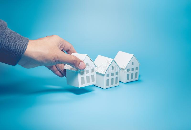 Business property,real estate and investment concepts with male hand and white model house on pastel color. Background stock image