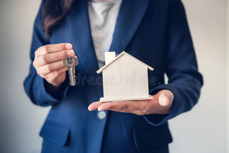 Business Real Estate and Residential Investment Concept, Broker Sell Agency of Property Estates Giving Keys for New Housing to. Customers While Holding House stock image