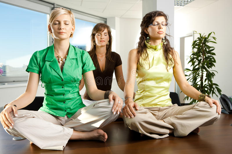 Business recteation. Young businesswomen sitting in yoga position on meeting room table stock image