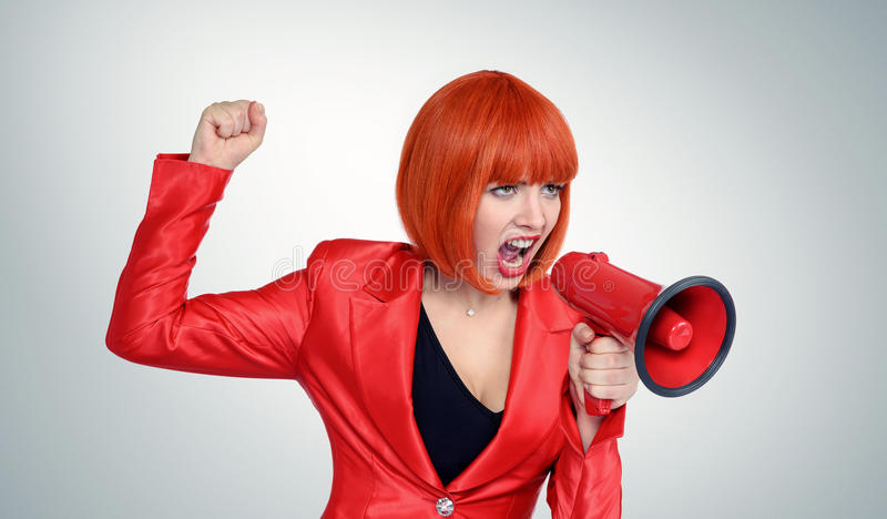 Business redhead woman in red screaming into a megaphone royalty free stock photography