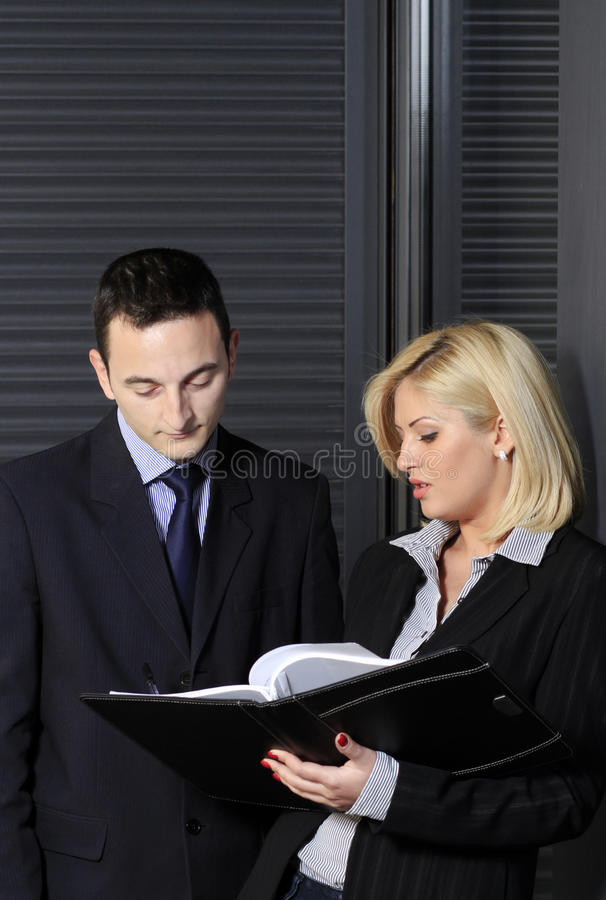 Business report. Assistant presenting the business report to her boss in an office environment stock image