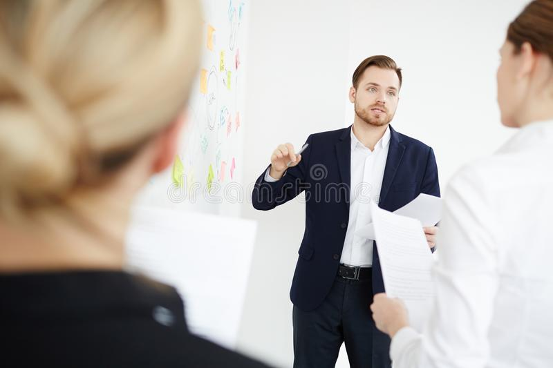 Business report. Confident businessman explaining his working idea while discussing plans with colleagues at meeting royalty free stock image