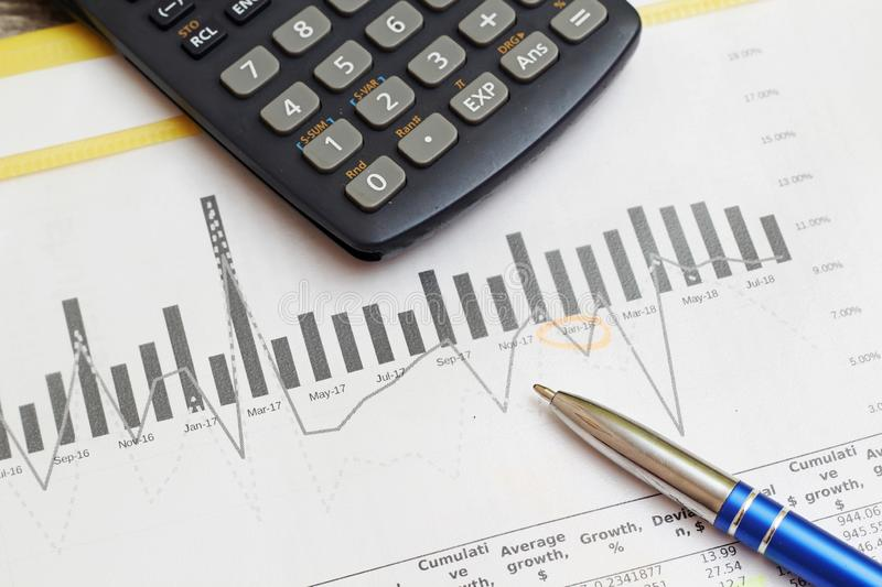 Business concept with a report and a calculator. Business report with figures and graphics, a calculator stock photos