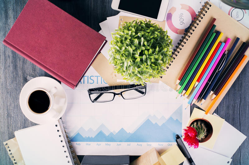 Business report and other items. Top view of messy office desktop with closed hardcover book, coffee cup, glasses, business report, plants and various stationery royalty free stock photography