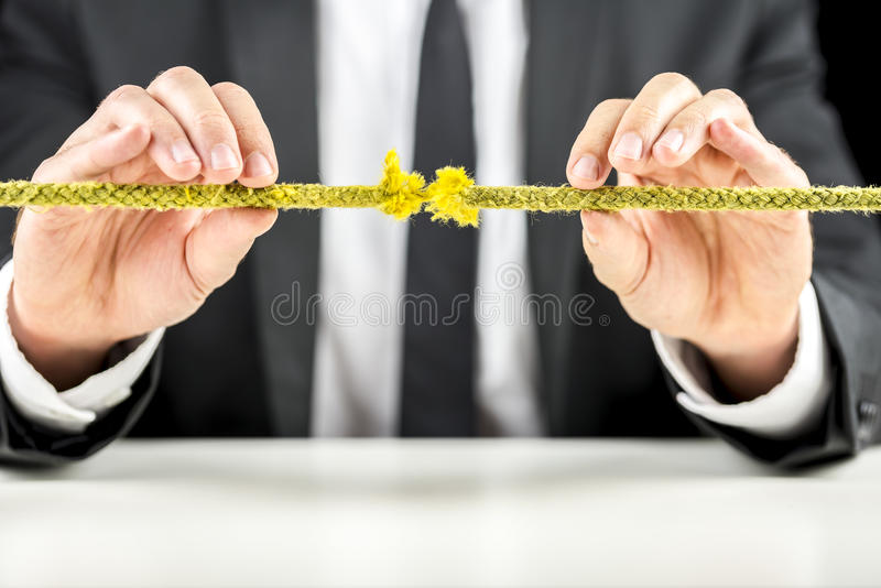 Business risk concept. Closeup of business man holding defective rope. Business risk concept royalty free stock photography