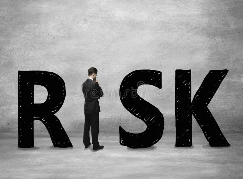 Business risk concept. With thoughtful businessman standing instead letter I on concerete background stock photos