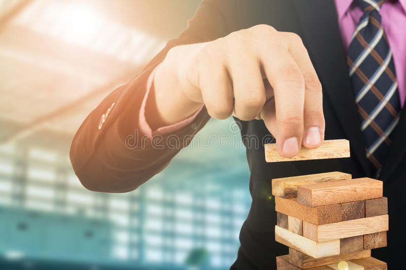 Business risk concept with wood jenga game.Businessman manage hi. S strategy royalty free stock photos