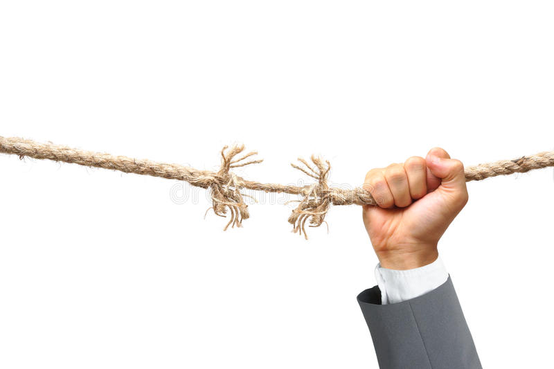 Business risk. Hand of a businessman hung on almost torn apart rope - Business risk concept stock photo