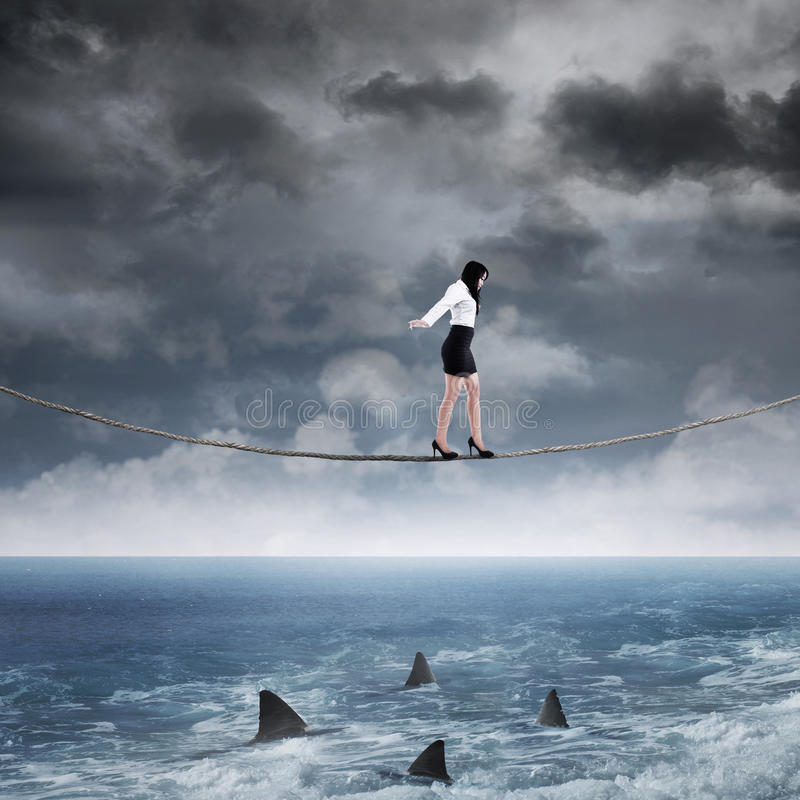 Business risk with woman on the rope. Concept of business risk with businesswoman walk on the rope above sea royalty free stock images