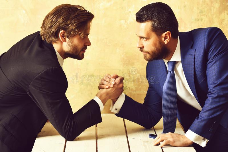 Business rivalry in office. Arm wrestling between two businessmans. Business rivalry. Businessmens in suits arm wrestling at office royalty free stock image