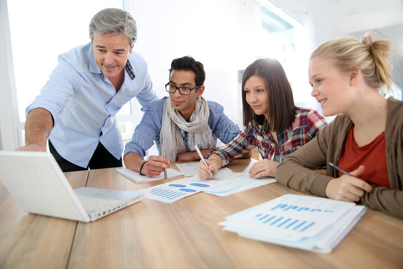 Business school training program. Business school students in marketing class with teacher royalty free stock photo
