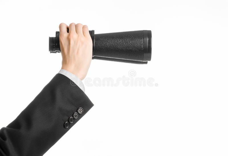 Business and search topic: Man in black suit holding a black binoculars in hand on white isolated background in studio stock photography
