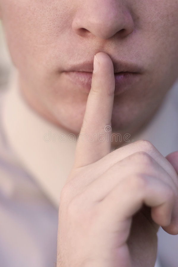 Business Secrets. Young man presses finger to lips in symbol requesting discretion through silence