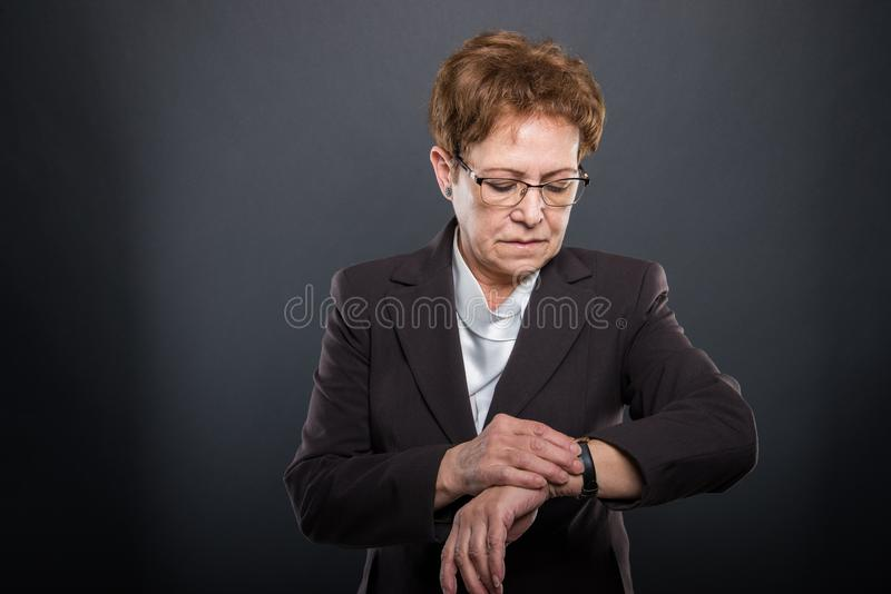 Business senior lady checking her wrist watch. Or being late on black background with copypsace advertising area royalty free stock photography