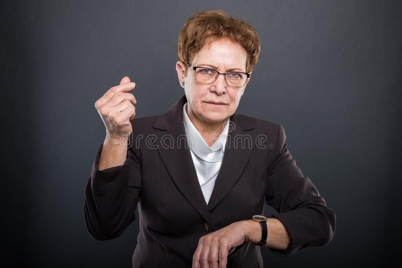 Business senior lady showing time is money gesture stock photography