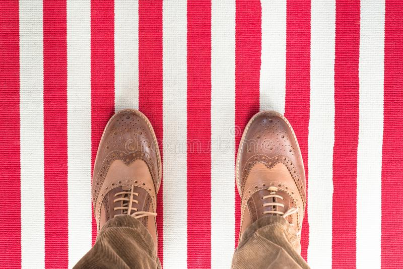 Business shoes on a red white striped carped stock photo