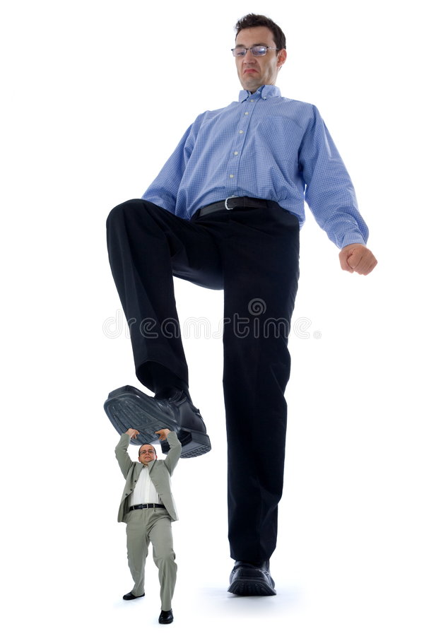 Business situation. Big businessman stepping on a small but strong fellow businessman. Conceptual view of how big companies want to destroy the little ones royalty free stock images
