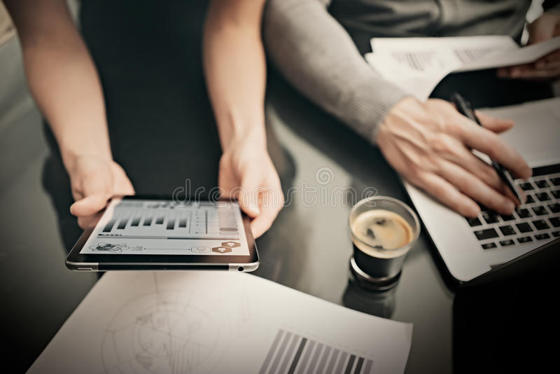 Business situation,meeting of marketing managers.Photo woman showing market reports modern tablet. Man using notebook royalty free stock image