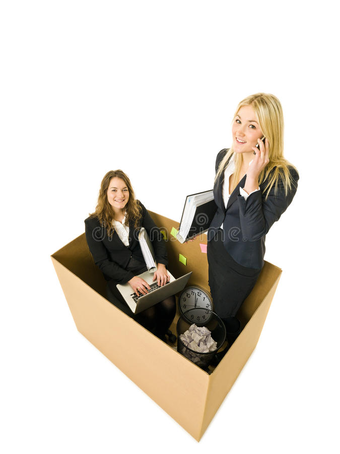 Business in a small office. Two Business women in a very small Cardboard office isolated on white background royalty free stock image