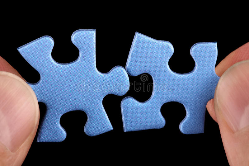 Business solutions. Hands holding two pieces of blue puzzle and fitting them together concept for solution or partnership stock image