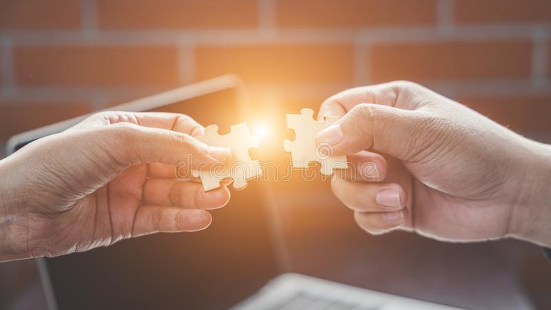 Business solutions, Businesswoman hand connecting jigsaw with businessman hand. success and strategy concept stock photography